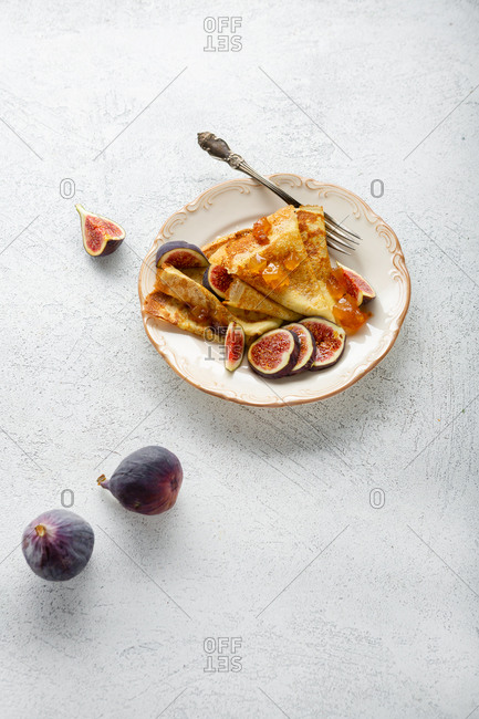 Crepes with jam and fruits on a plate
