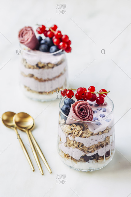 Delicious granola with golden spoons on a marble table