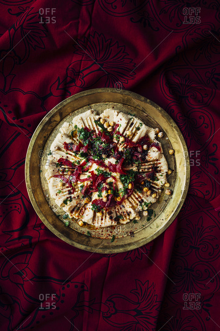 Top of view hummus on a red ethnic tablecloth
