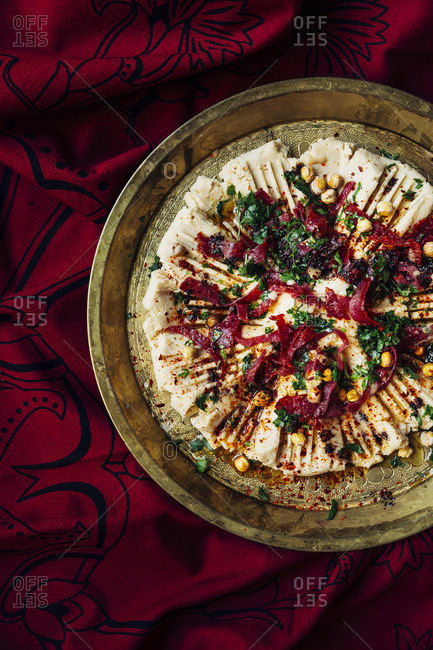 Overhead view hummus on a red ethnic tablecloth