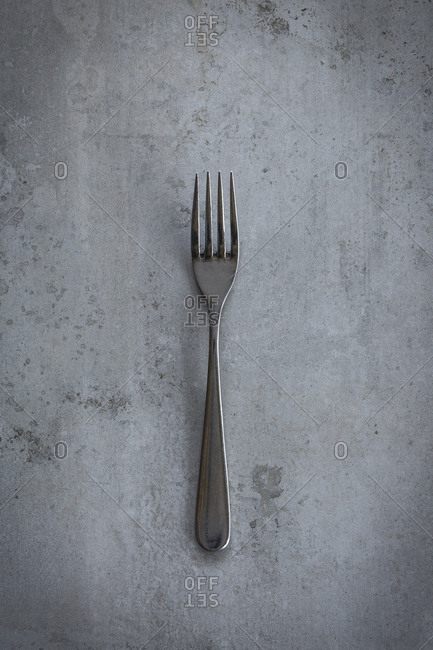 Single fork on a grey surface
