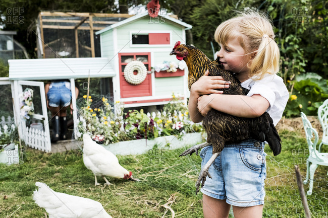 Blond girl standing in a garden in front of hen house, holding brown chicken.