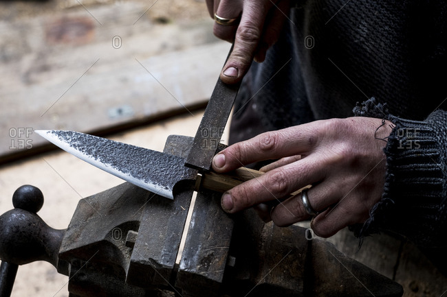 High angle close up of person working on handmade knife using a file.