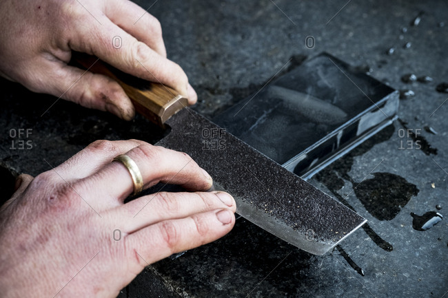 High angle close up of person sharpening handmade knife on a whetstone.