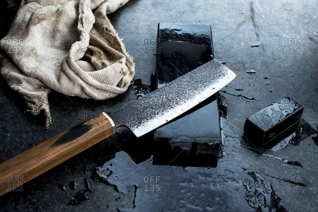 High angle close up of handmade knife on whetstone.
