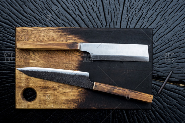 High angle close up of two handmade knives on wooden cutting board.