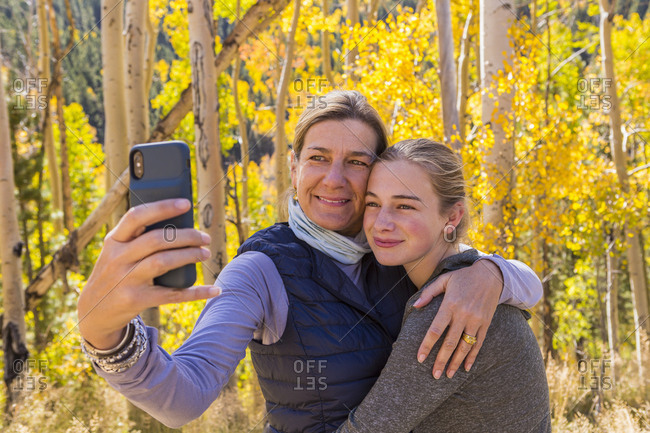 portrait of mother and her 13 year old daughter with autumn aspens in background, taking a selfie picture