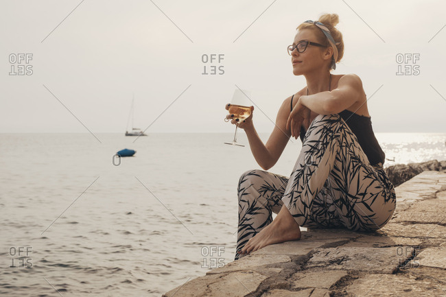 Beautiful stylish woman sitting by the sea and daydreaming while dinking wine.