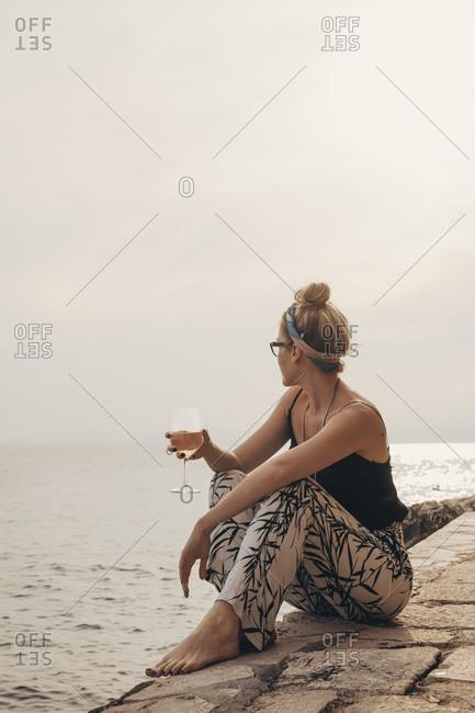 Pretty stylish woman sitting on seacoast and enjoying sunset drinking wine.