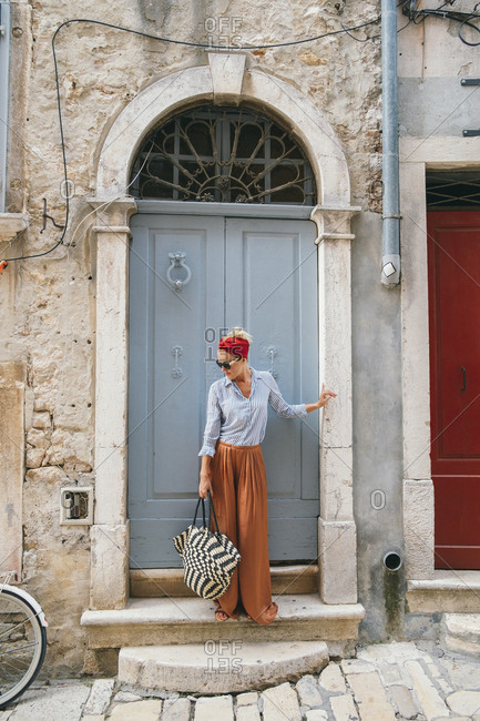 Beautiful stylish woman standing at Mediterranean old town and posing next to building with unique architecture.