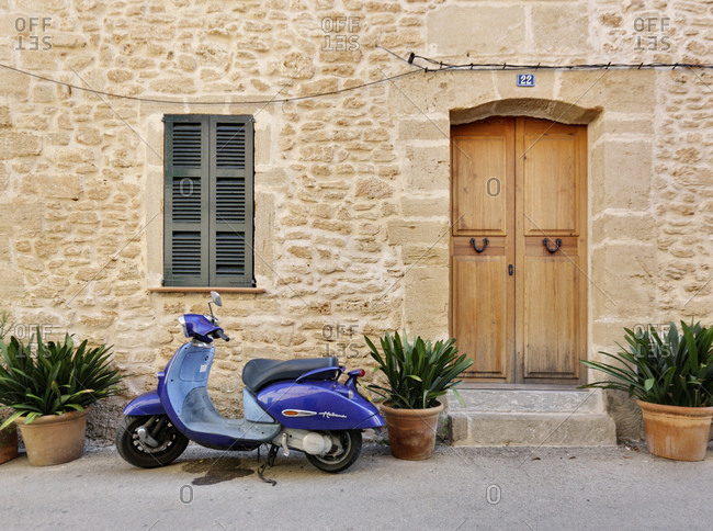 October 12, 2016: Spain, Majorca, alcudia, house, side of the street, number 22, facade, door, window, shutters closed, potted plants, motor scooter, pedestrian area