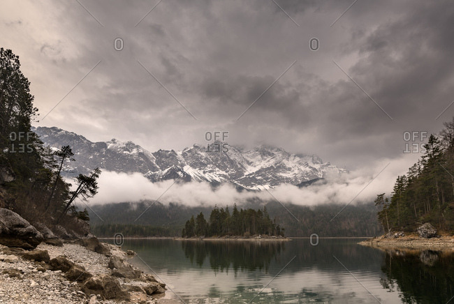 The eibsee near grainau in bavaria, with the sasseninsel and in the background the cloudy zugspitze.