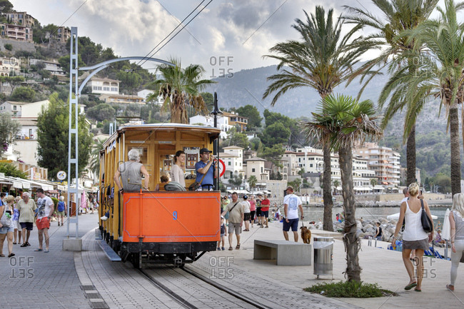 October 8, 2016: Spain, Majorca, port de soller, streetcar, passengers on the rear stage, people, palms, pedestrian area, shore