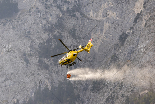 May 11, 2017: Two helicopters of the Oamtc in forest fire-fighting operation near innsbruck in tyrol, austria.