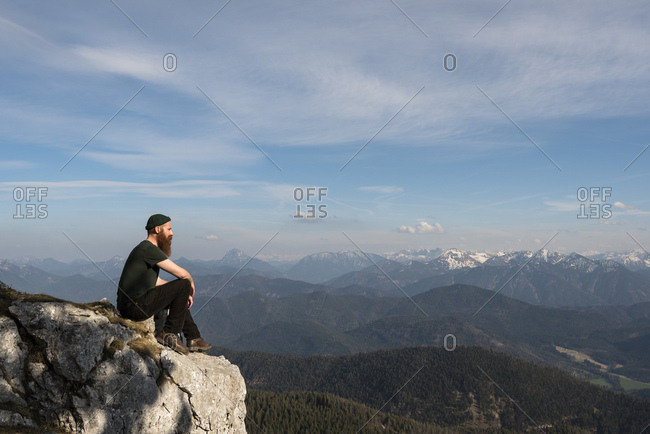 A bearded mountaineer sitting on a rock and looking to the karwendel mountains.