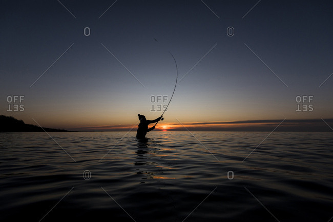 Angler fishing in the baltic sea at sundown standing in water.