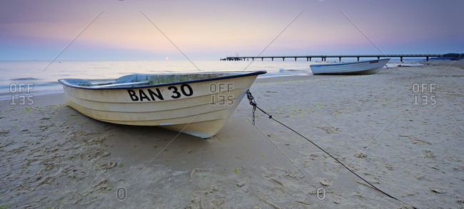 September 11, 2016: Germany, mecklenburg-western pomerania, usedom island, ostseebad bansin, fishing boats on the beach at sunrise, behind it the sea bridge