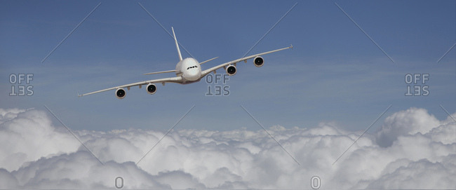 Airbus a380 in the flight from the front above the clouds [m]