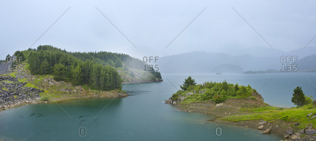 Panoramic picture of a reservoir with overcast rain clouds