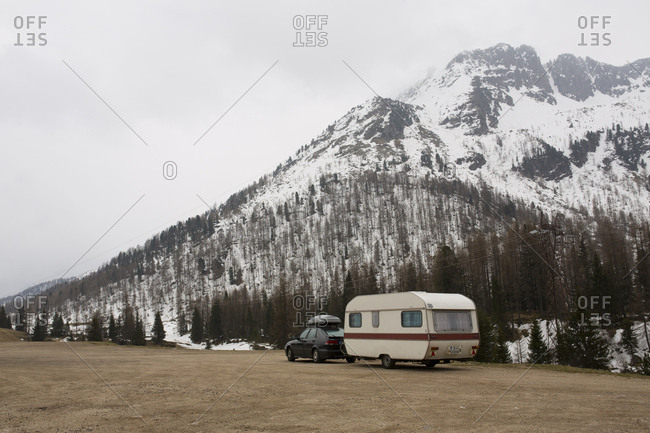 April 25, 2015: Caravan trailer on sand surface in front of cloud-covered mountain landscape