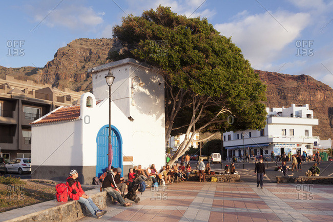 December 29, 2014: Tourists on the market square at sundown, district la playa in valle gran rey, la gomera, canary islands, spain