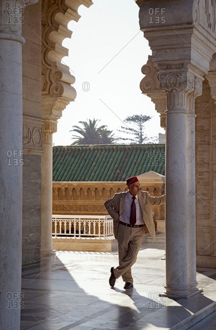 December 4, 2015: Man standing agianst a column rabat, mausoleum, architecture, morocco