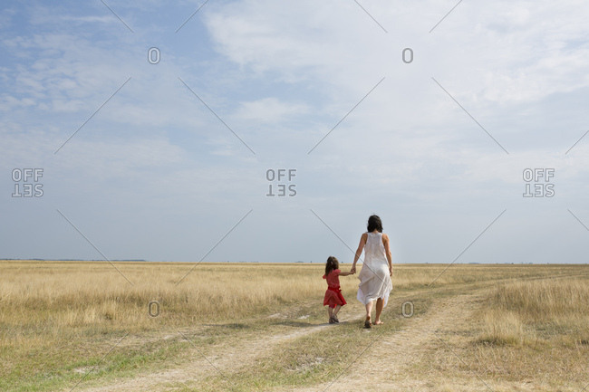 30-40 years old mother with 4-6 years old child walking hand in hand on a country lane