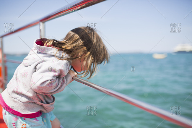 4-6 years old girl standing on a boat, view in the water