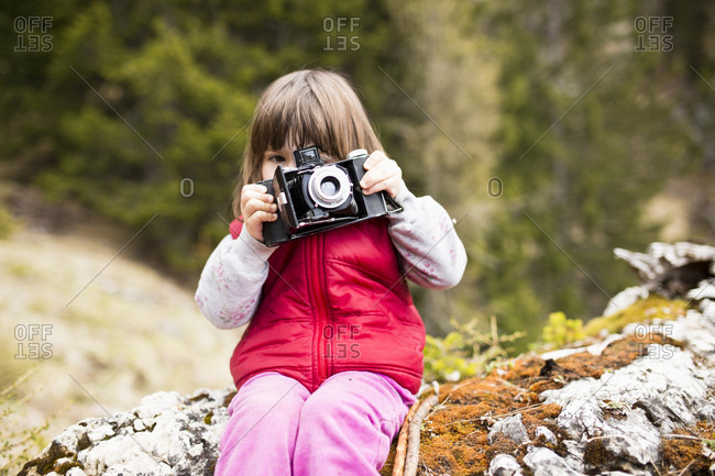 3-6 years old girl in red waistcoat taking photos with an old camera