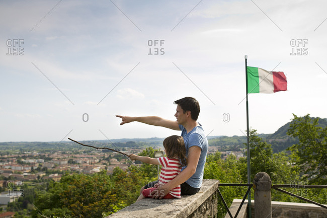 30-40 years old father sitting with 4-6 years old daughter on a wall, view above the town