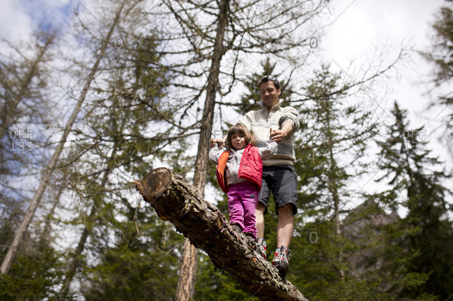 30-40 years old father balancing on a trunk in the forest with 4-6 years old daughter