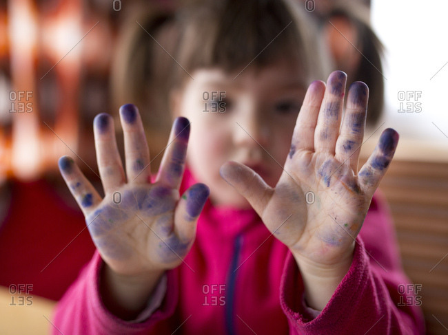 4-6 years old child with plaits holding blue painted fingers in the camera