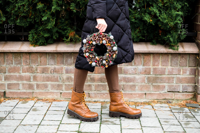 The pretty girl is holding colorful handmade Christmas wreath with cones and glistening balls in her hands