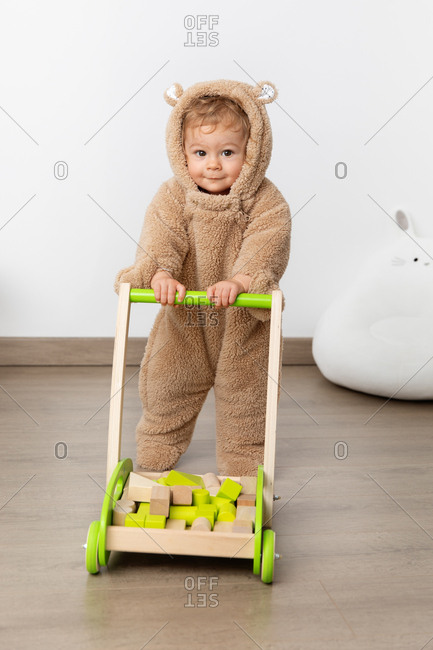 Baby in hooded bear suit pushing a walker