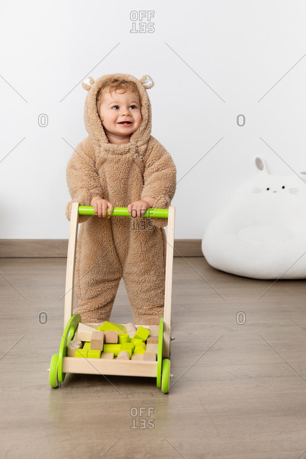 Smiling baby in hooded bear suit learning to walk with trolley
