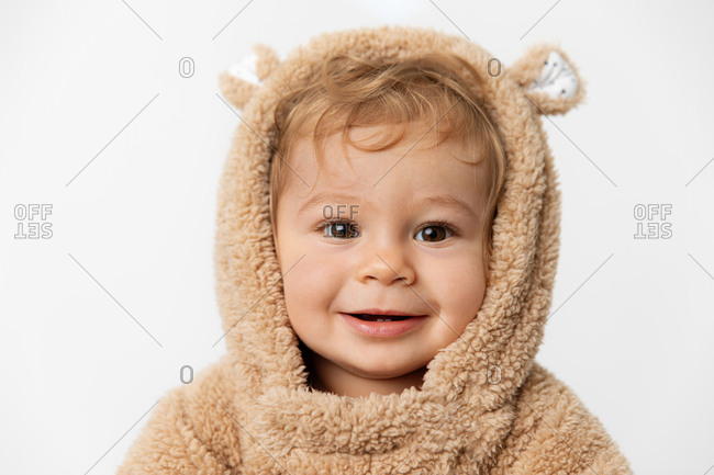 Portrait of smiling baby in hooded bear suit