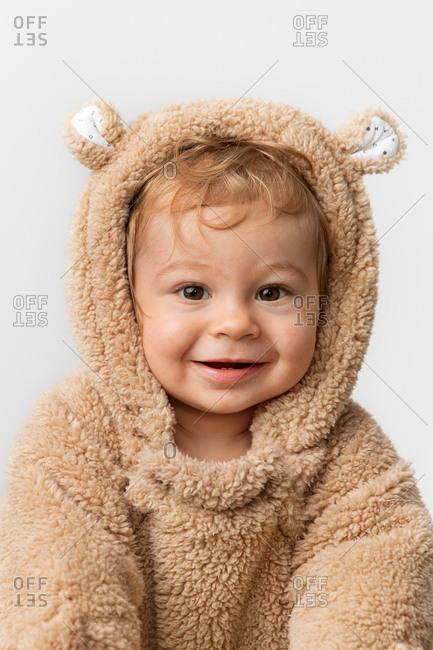 Cute smiling baby in hooded bear suit