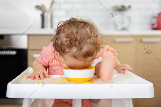 Toddler in high chair eating pasta straight from bowl