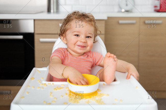 Smiling baby in high chair eating pasta with hands