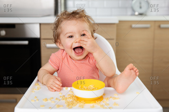 Cute baby eating a handful of pasta with foot on table