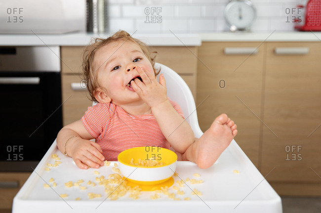 Happy toddler eating pasta in high chair with foot on table