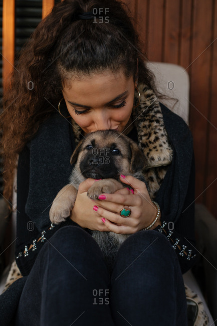 Portrait of a brunette girl kissing and snuggling a puppy