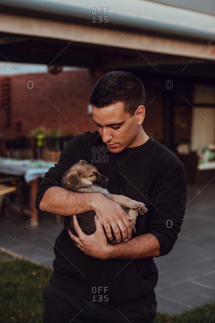Portrait of a man cuddling with a puppy