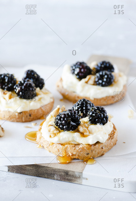 Close up of toast with cheese, fresh blackberries, walnuts and honey