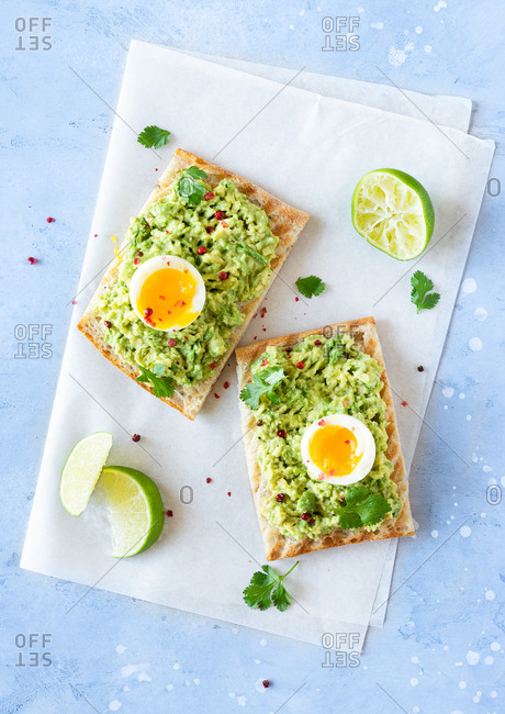 Overhead view of avocado toast with soft-boiled eggs and lime