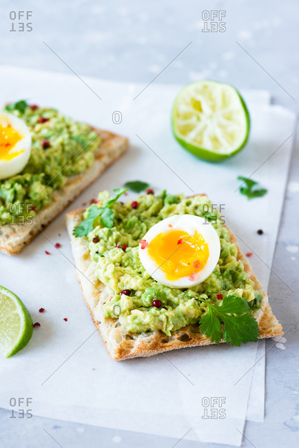Close up of avocado toast with soft-boiled eggs and lime