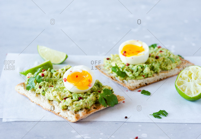 Avocado toast with soft-boiled eggs and lime over blue backdrop