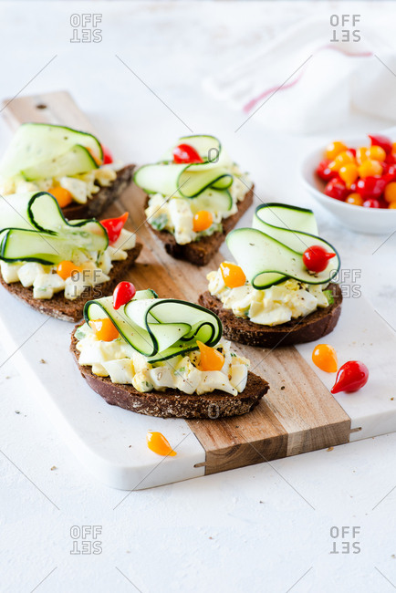 Egg salad pumpernickel sandwiches with cucumber and pickled peppers served on board