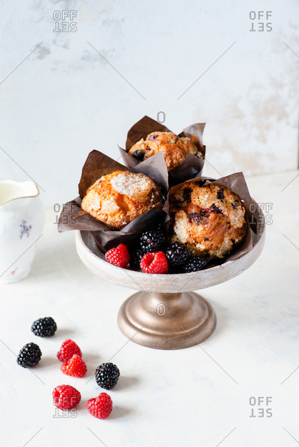 Muffins with mixed berries in paper cupcake holder on cake stand fresh raspberries and blackberries on side