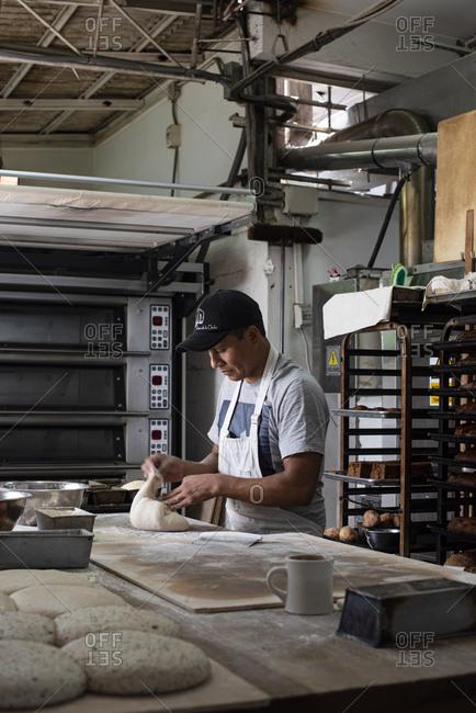 Cusco, Peru - April 2, 2019: Man working in a bread bakery